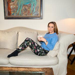 Ich sitze auf der Couch und trage einen hellblauen Pullover und eine geblümte Hose.