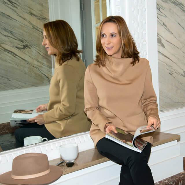 Frau sitzend mit Tasse und Zeitschrift.